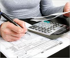 An accountant is filling a tax return form. We can see her holding a pen and calculator.