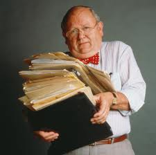 Older man is caring a huge pile of papers--the accounting standards