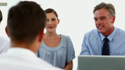 A scene from an interview. Two HR managers observe the job applicant closely